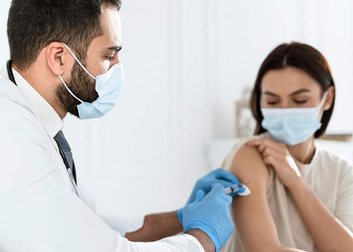 Doctor Vaccinating Young Woman
